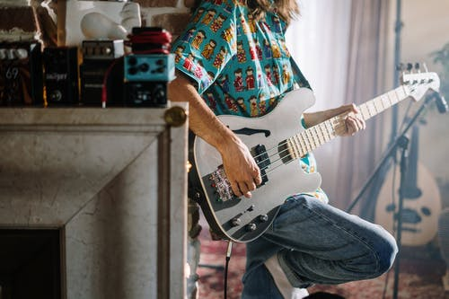 Woman in Red Blue and White Plaid Button Up Shirt Playing Electric Guitar