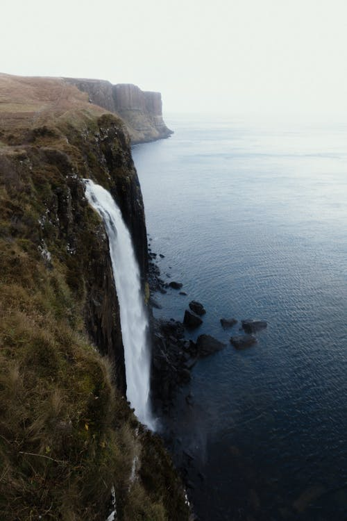 Amazing waterfall streaming through rocky cliff and emptying into  ocean