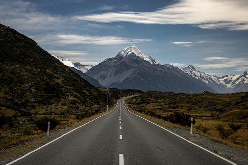 Gray Concrete Road Near Mountain Under White Clouds