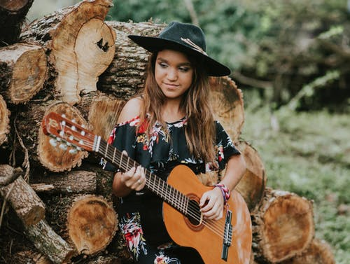 Woman in Black Hat Playing Acoustic Guitar
