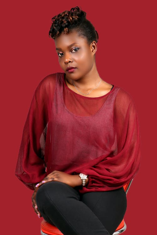 Confident black woman in red blouse and jeans in studio
