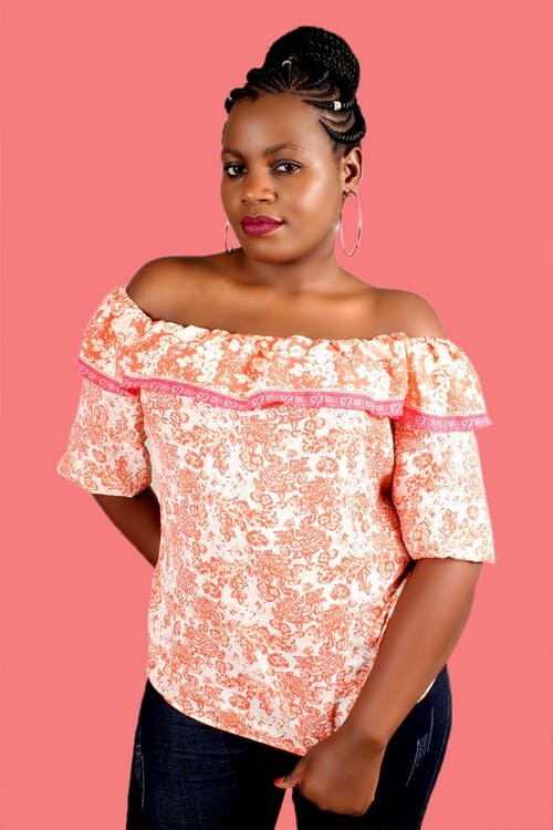 Confident plump ethnic woman in casual clothes with bare shoulders looking at camera while standing against pink background
