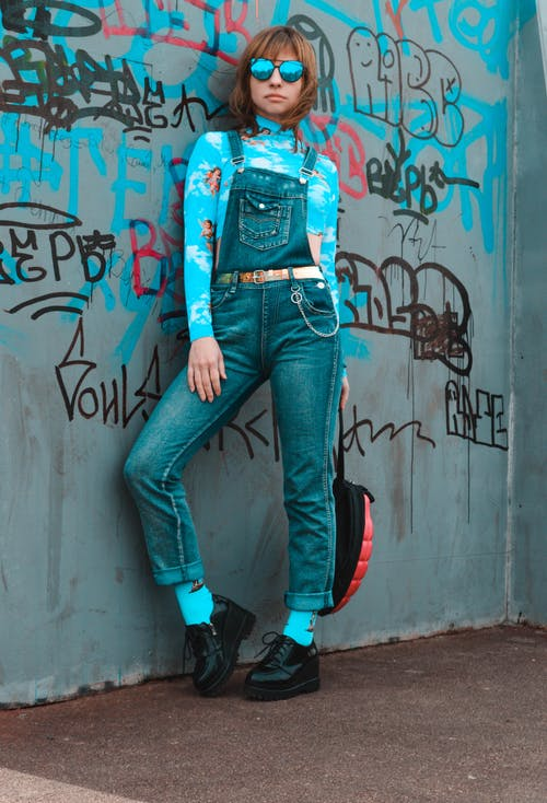 Full length of young slim female in denim jumpsuit with blue shirt and sunglasses chilling near shabby vandalized wall