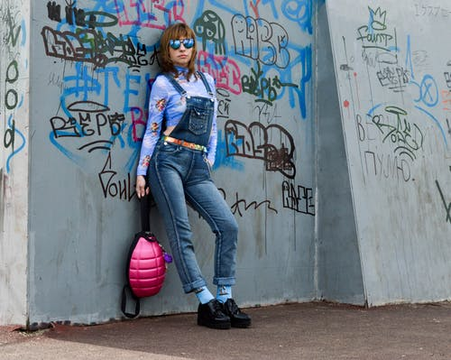 Stylish female in sunglasses leaning on grunge wall