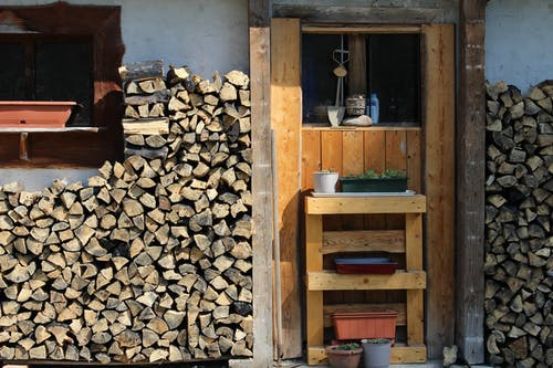 Rural house backyard with stacks of firewood and decorative items on window with pot plants