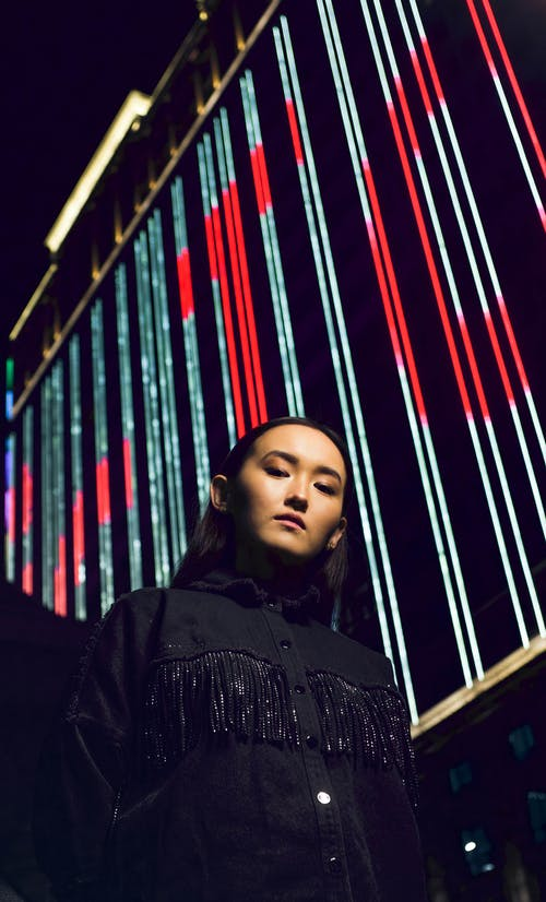 Serious Asian woman standing at billboard