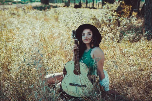 Woman in White Tank Top and Black Hat Holding White Acoustic Guitar Sitting on Brown Grass
