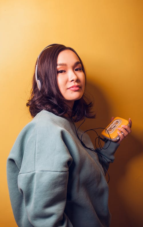 Side view of young Asian woman in warm sweater with headphones listening to music via vintage player looking at camera