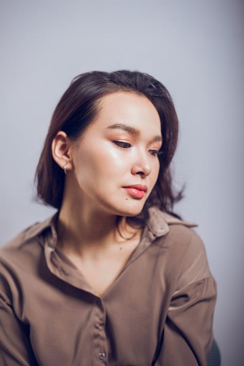 Thoughtful woman with makeup in light brown blouse