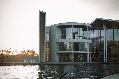White and Black Concrete Building Near Body of Water