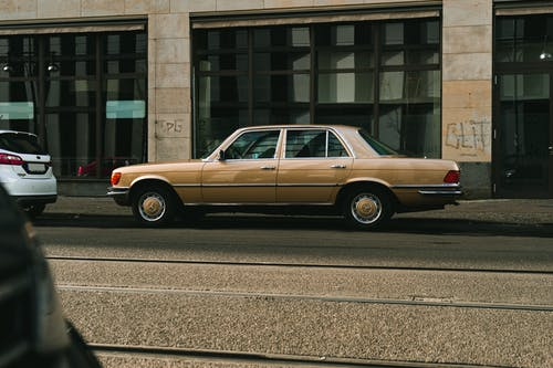 Brown Sedan Parked on Gray Concrete Road