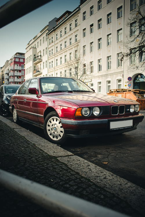 Red and White Bmw M 3 Parked on Sidewalk