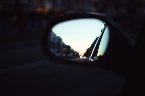 Car Side Mirror Showing City Buildings