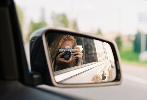 Person Taking a Self Portrait on a Rear View Mirror