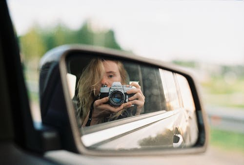 Woman Taking a Self Portrait on a Rear View Mirror