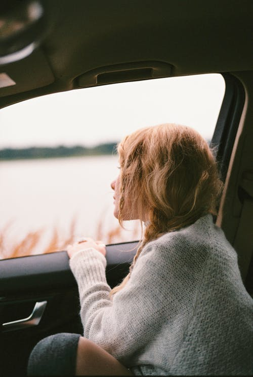 Woman in Sweater Sitting Inside Car Looking Out the Window