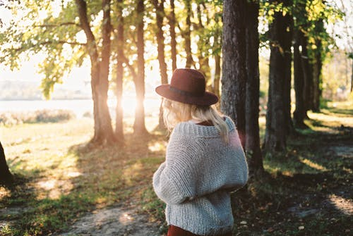 Woman in Knit Sweater and Brown Hat Standing near Trees