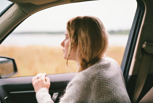 Woman in Sweater Inside a Car