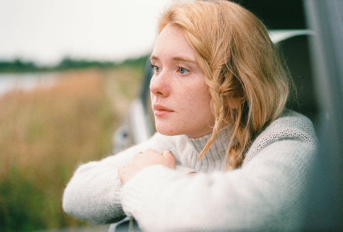 Woman in White Sweater thinking