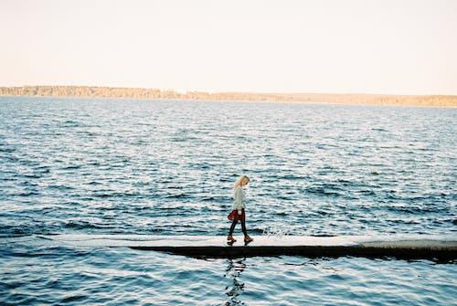 Woman Walking on a Sea Dock