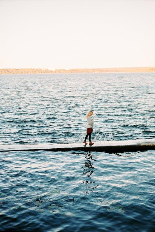 Woman Walking on a Dock