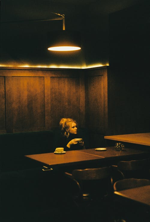 Woman Sitting at the Table In Dim Light