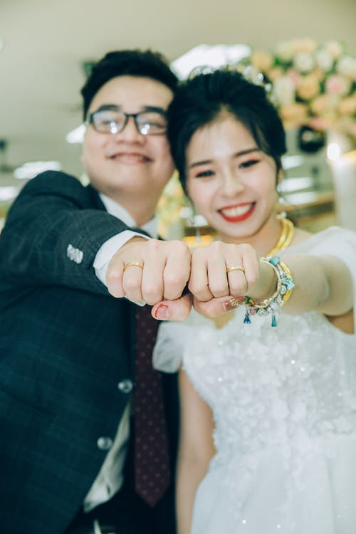 Delighted newlywed couple showing wedding rings