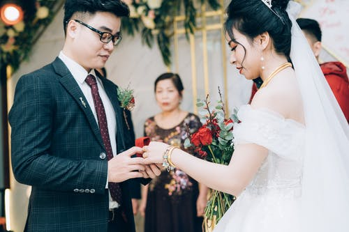 Side view of crop ethnic bride with makeup in dress with bridal bouquet and groom in suit with eyeglasses preparing rings during marriage ceremony in decorated hall behind parent