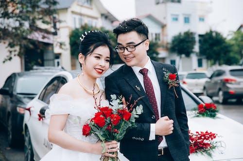Happy elegant Asian couple near car on wedding day