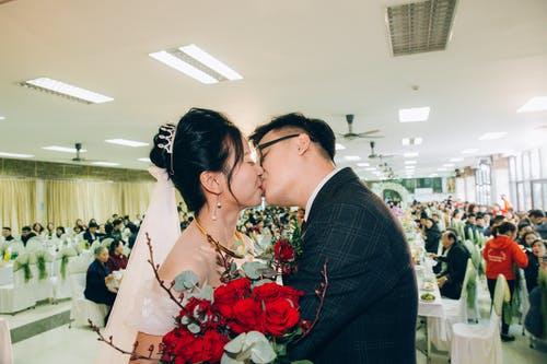 Side view of stylish Asian bride with flower bouquet and groom in suit with closed eyes kissing each other while standing in hall behind tables with guests on wedding day