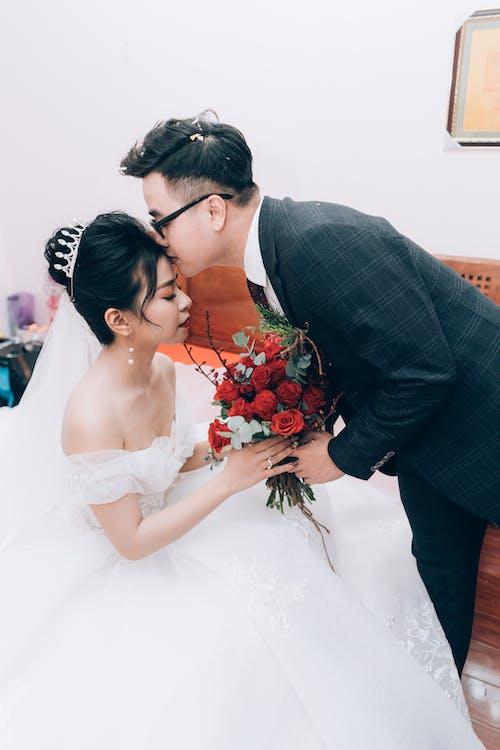 Unrecognizable groom kissing elegant Asian bride on wedding day