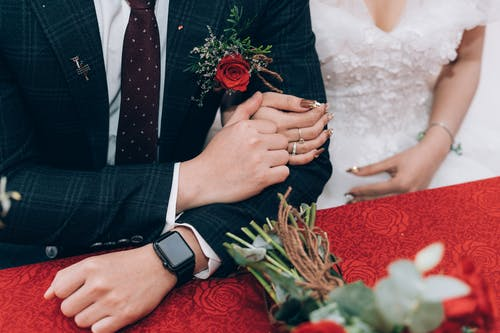 From above of crop unrecognizable husband in suit with smart watch and wife in wedding dress with manicure sitting together at colorful table with flowers after getting married