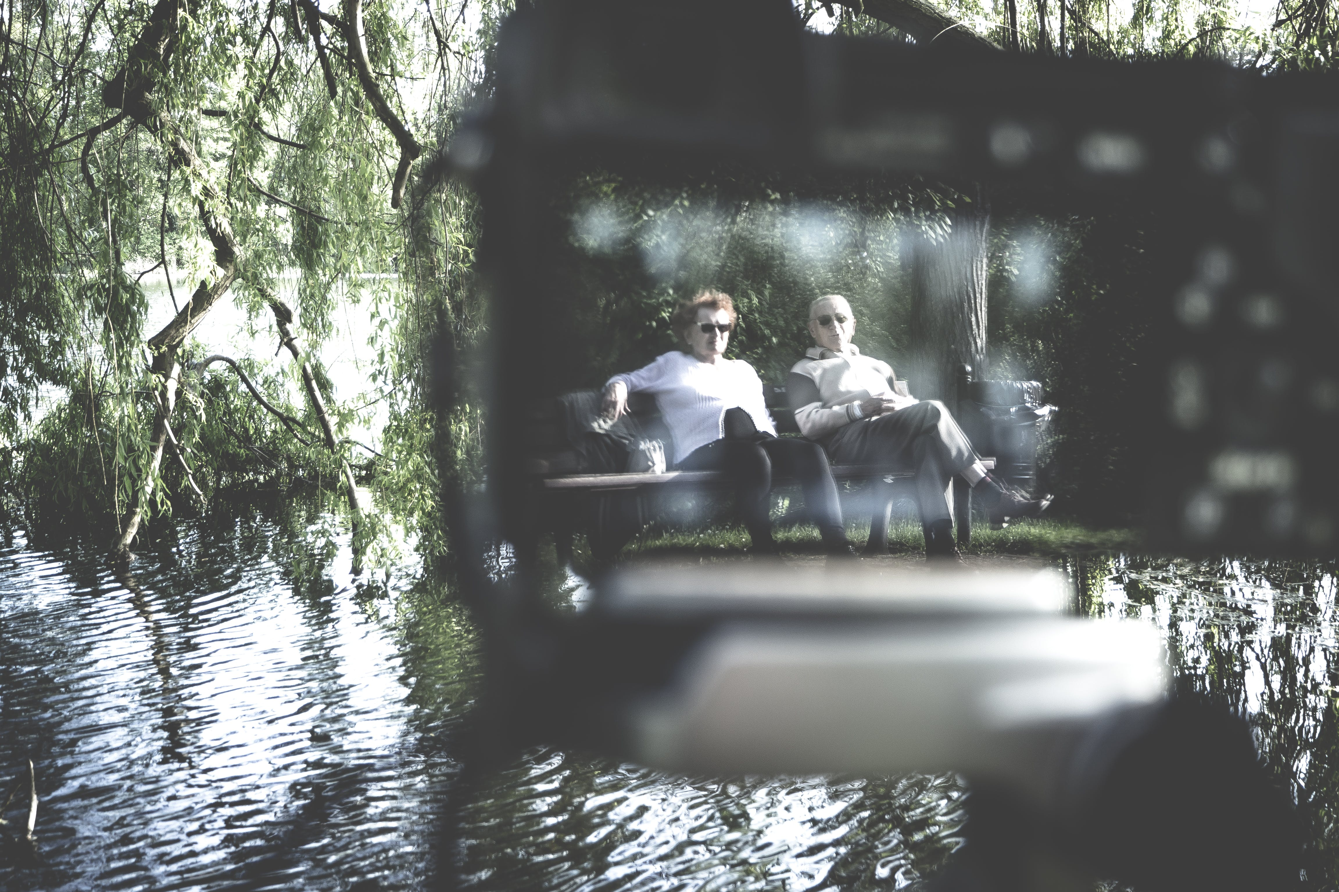 Selective Focus Photography of Two Men Sitting on Bench
