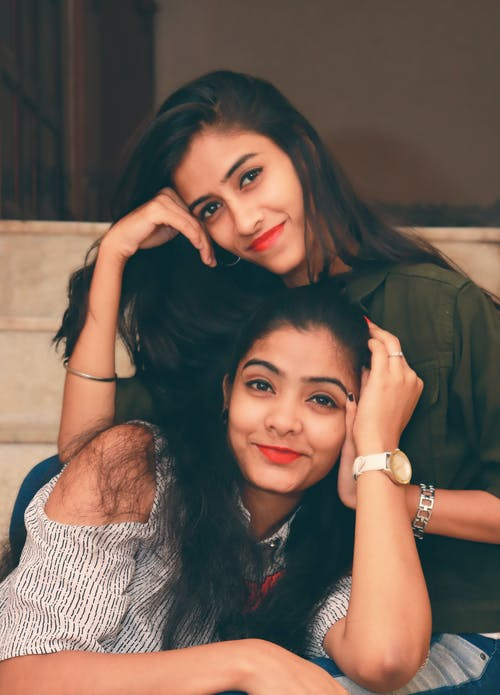 Young smiling women in wristwatches and casual wear with makeup looking at camera while resting leaned on hands on wooden bench