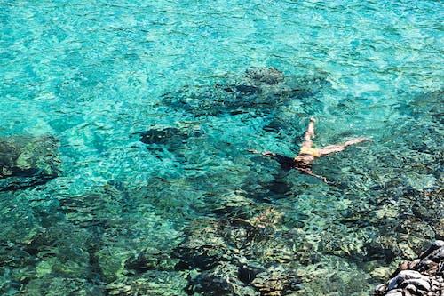 Woman in Blue Bikini Swimming on Sea