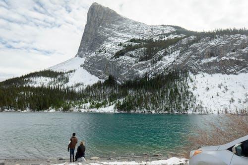 2 Person Standing on Beach Near Mountain