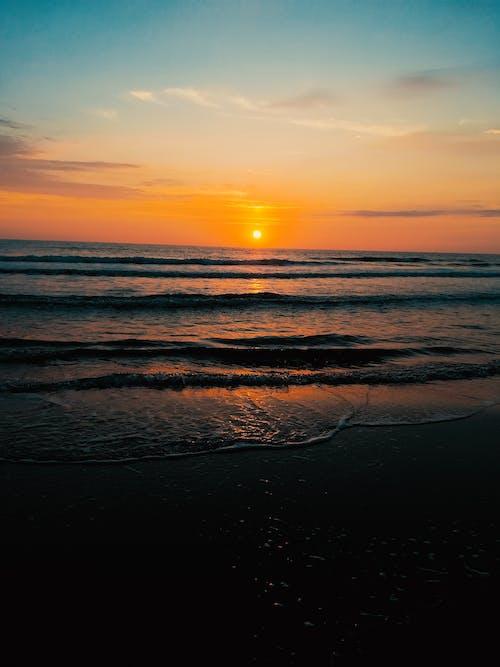 Picturesque view of sun setting over wavy foamy sea washing sandy beach at sundown