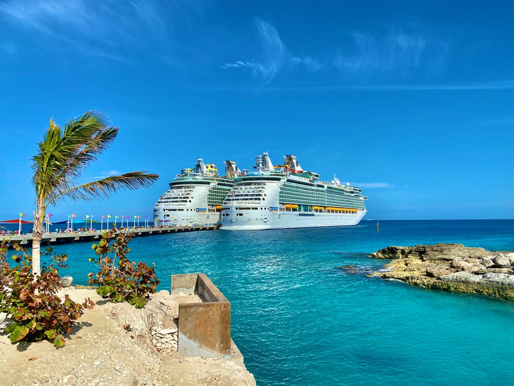 Similar big cruise ships sailing on rippled sea surrounded by small dry exotic islands and boardwalk under colorful blue sky in daylight in harbor
