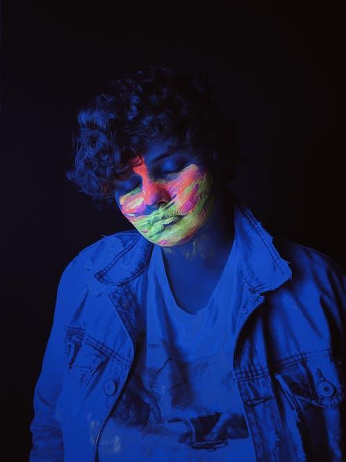 Teenage boy standing under neon light