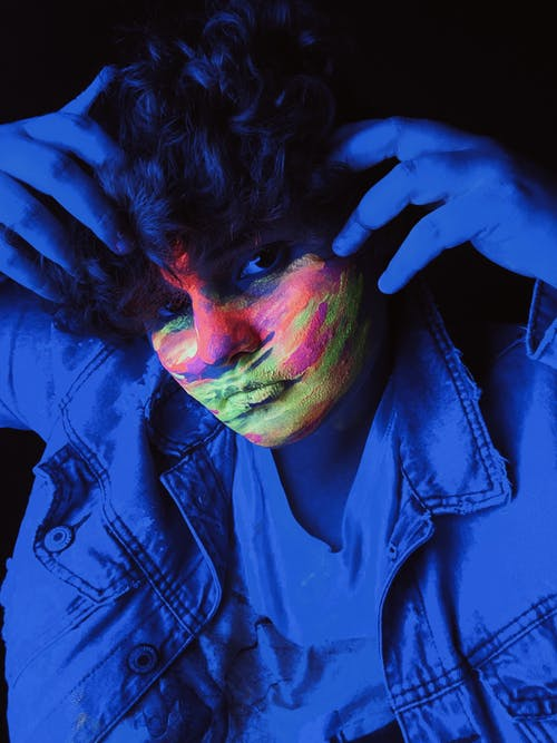 Teen curly haired boy with painted face standing under neon light and looking at camera
