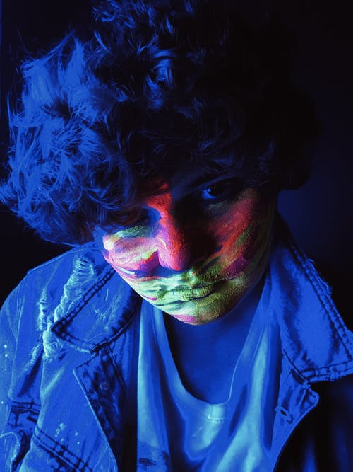 Teenage boy with dye on face in neon light