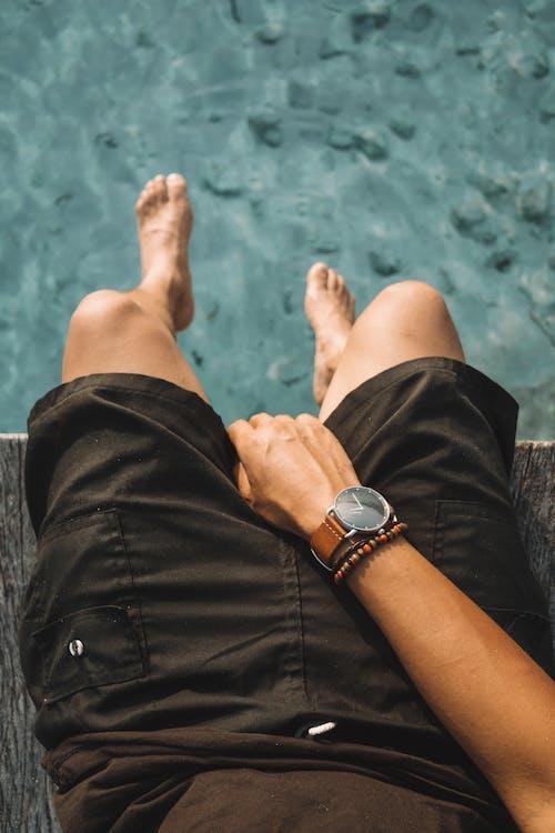 Person in Black Denim Shorts Wearing Silver Watch