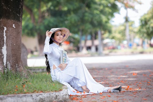 Woman in White Long Sleeve Dress Sitting on Gray Concrete Pavement