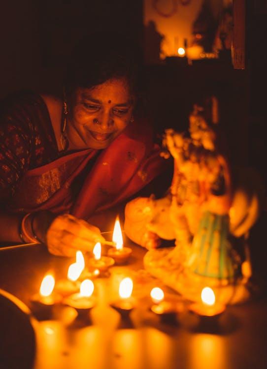Woman Lighting Diya Oil Lamps