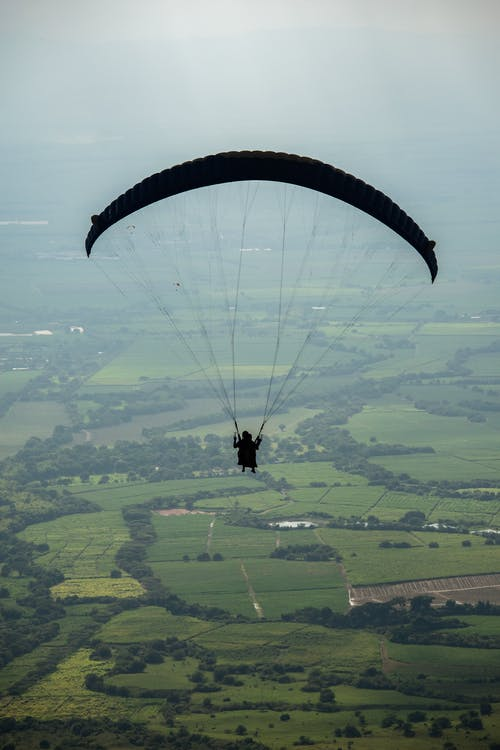 Faceless person flying paraglider over green countryside