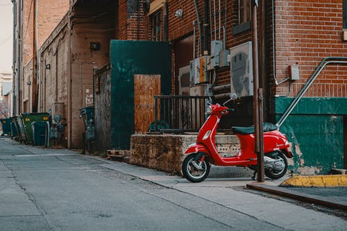 Red scooter on backstreet in city