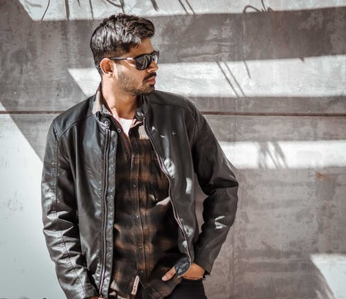 Man in Black Leather Jacket Standing Beside Gray Wall