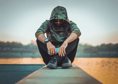 Man in Green and Black Camouflage Hoodie and Black Denim Jeans