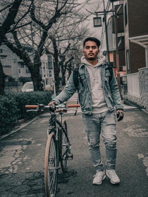 Man in Gray Jacket and Blue Denim Jeans Standing on Road With Bicycle