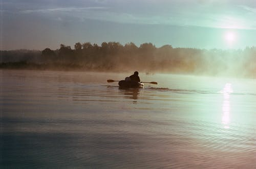 Anonymous man in boat on misty lake